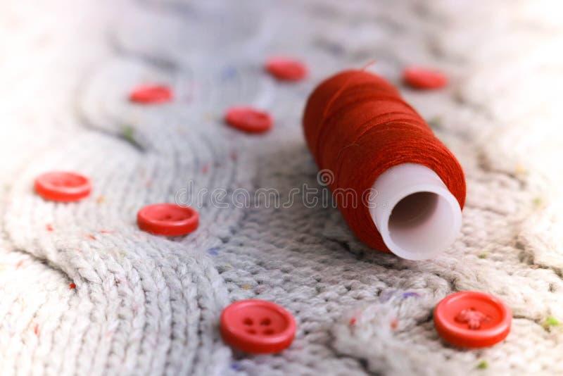 Mjuk varm naturlig tröja, tyger med en stucken modell av garn och röda små runda knappar för att sy och en skein av den röda tråd royaltyfria bilder