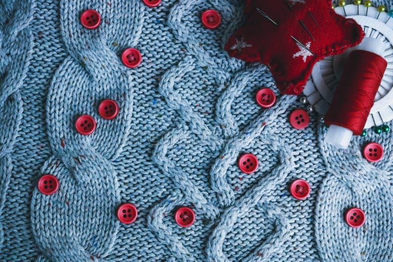Mjuk varm naturlig tröja, tyger med en stucken modell av garn och röda små runda knappar för att sy och en skein av den röda tråd arkivbilder
