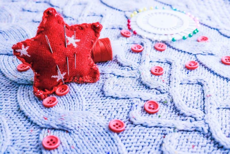 Mjuk varm naturlig tröja, tyger med en stucken modell av garn och röda små runda knappar för att sy och en skein av den röda tråd royaltyfria foton