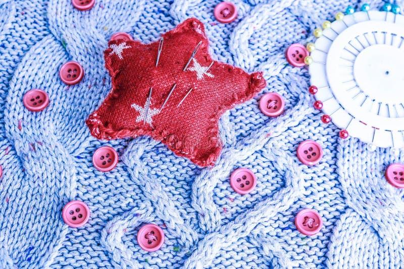 Mjuk varm naturlig tröja, tyger med en stucken modell av garn och röda små runda knappar för att sy och en skein av den röda tråd arkivbild