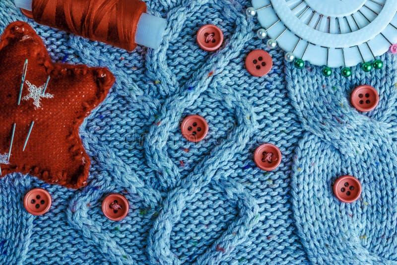 Mjuk varm naturlig tröja, tyger med en stucken modell av garn och röda små runda knappar för att sy och en skein av den röda tråd fotografering för bildbyråer
