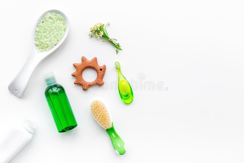 Mjuka badskönhetsmedel för ungar med kamomill Flaskor, salt brunnsort, tandborste och leksak på bästa sikt för vit bakgrund fotografering för bildbyråer