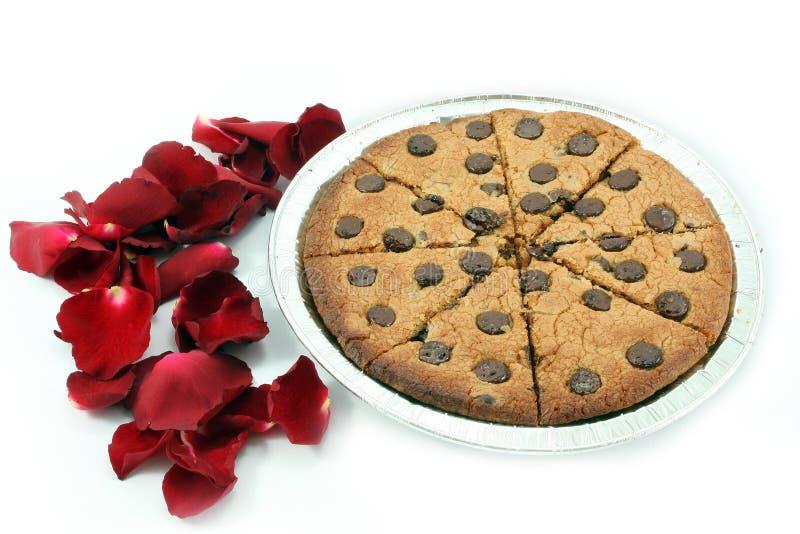 Mjuka choklade kakor med rosa kronblad på vit bakgrund royaltyfri bild