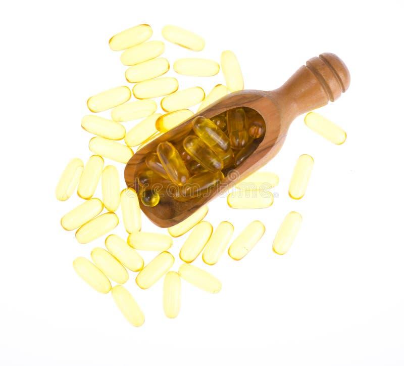 Mjuka gelatinkapslar för gult vitamin med den oljiga drogen och det näringsrika tillägget, träskedar, skopa arkivbild