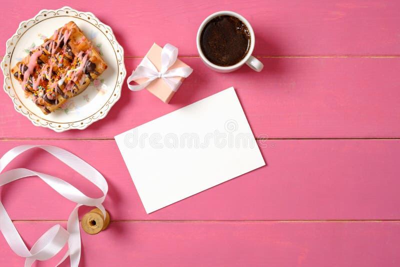 Mjuka kvinnas skrivbord drinking glass straws Tomt pappers- kort, rulle med bandet, g?vaask, kopp kaffe, smaklig kaka p? rosa woo royaltyfri foto