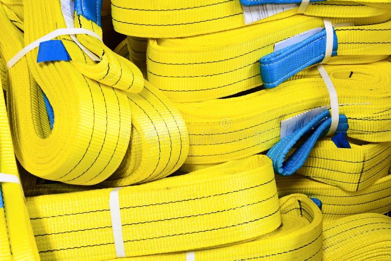 Mjuka lyftande remmar för gult nylon som staplas i högar royaltyfri bild