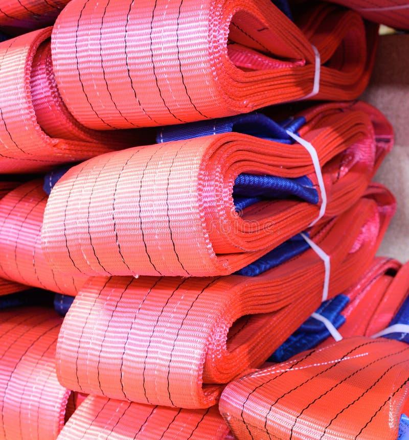 Mjuka lyftande remmar för rött nylon som staplas i högar arkivfoto
