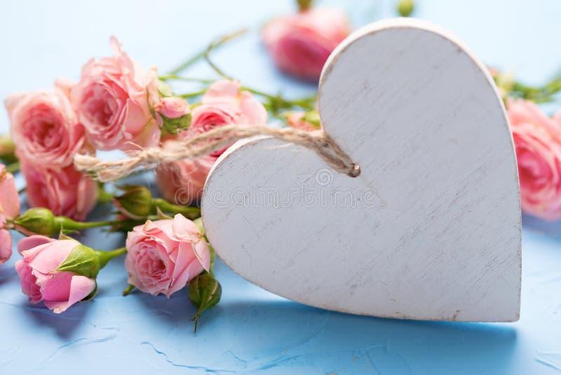 Mjuka rosa rosblommor och dekorativ vit hjärta på textur royaltyfria foton