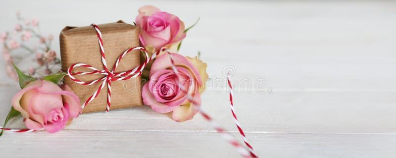 Mjuka rosa rosor med en gåva fotografering för bildbyråer