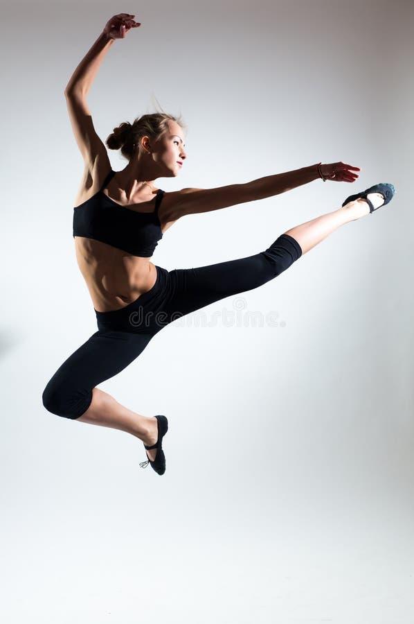Mjukhet, nåd, melodi och plast- av den gymnastiska flickan Hedra hoppet i luften av den trevliga unga flickan fotografering för bildbyråer