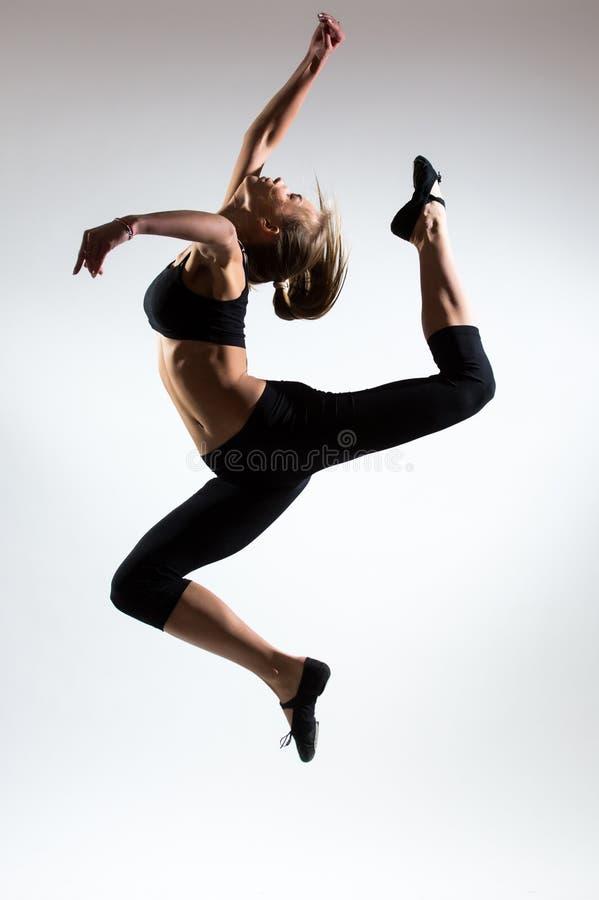 Mjukhet, nåd, melodi och plast- av den gymnastiska flickan Hedra hoppet i luften av den trevliga unga flickan royaltyfri foto