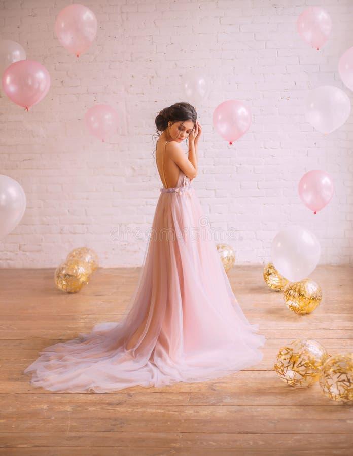 Mjukt foto av en flicka med mörkt hår i en fantastisk proper frisyr som är iklätt ett storartat rosigt med en purpurfärgad klänni arkivbild