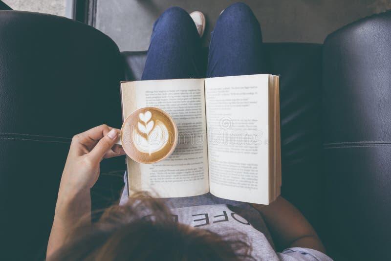 Mjukt foto av unga flickan som läser en bok och dricker kaffe, överkant royaltyfria foton