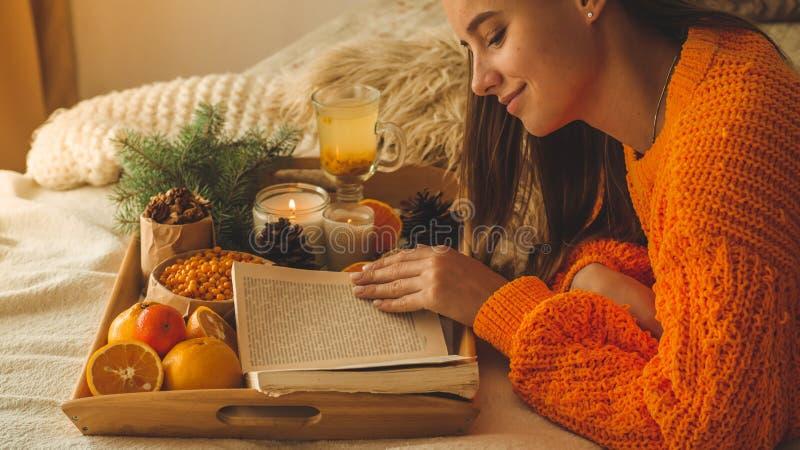 Mjukt hemtrevligt foto av kvinnan i varm orange tröja på sängen med kopp te och frukt Flicka som sitter på sängen med gamla böcke royaltyfri bild