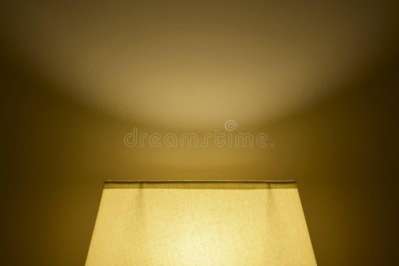 Mjukt ljus från en lampskugga på väggen i ett mörkt rum Panelljus underifr?n royaltyfria foton