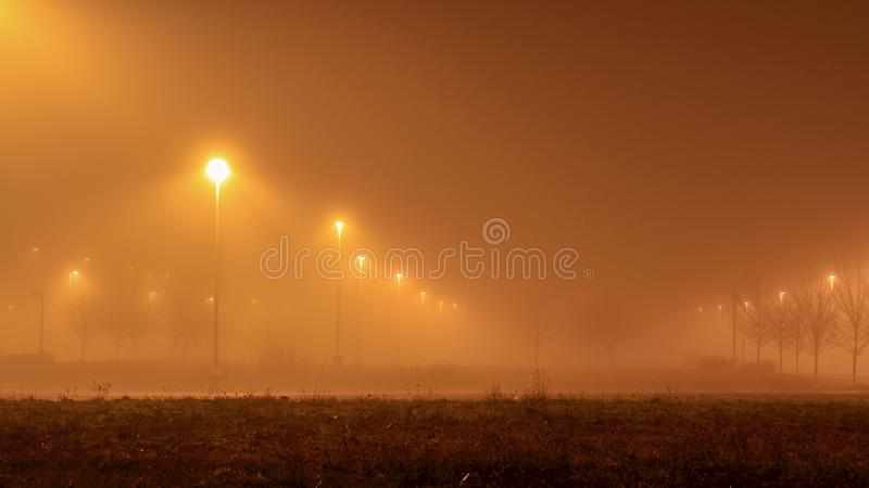 Mjukt utbrett ljus från ljusa ställningar på en parkeringsplats i den dimmiga aftonen royaltyfria bilder