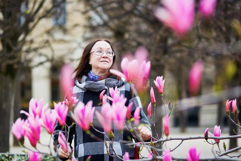 MKiddle aged woman in Paris on a spring day. Beautiful middle aged woman in Parisian park on a spring day admiring pink magnolia in full bloom stock photography