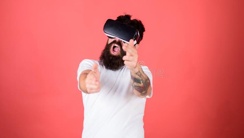 Mknąca galeria VR Obsługuje brodatego modnisia z rzeczywistości wirtualnej słuchawki na czerwonym tle Pierwszy osoba strzelająceg obrazy stock