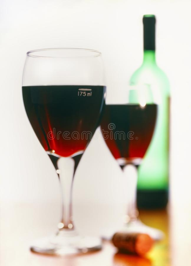 125ml measure of red wine in a set of 2 glasses with a green wine bottle in the background stock photo