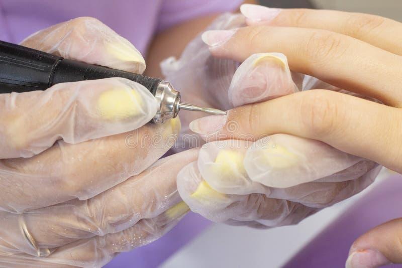Mleć i przetwarzać gwoździa talerz manicure'u mistrz robi narzędzia robić manikiur klient gwoździa froterowanie przed stosować ge obrazy stock