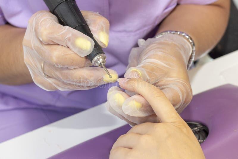 Mleć i przetwarzać gwoździa talerz manicure'u mistrz robi narzędzia robić manikiur klient gwoździa froterowanie przed stosować ge obraz stock