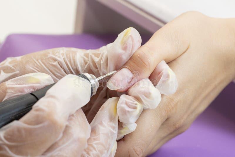 Mleć i przetwarzać gwoździa talerz manicure'u mistrz robi narzędzia robić manikiur klient gwoździa froterowanie przed stosować ge zdjęcia stock