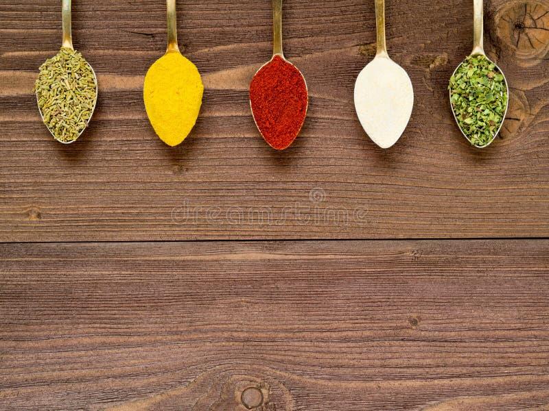 Mleć pikantność - czosnek, turmeric, papryka, rozmaryn, oregano, Złote łyżki na brown drewnianym stole obraz royalty free