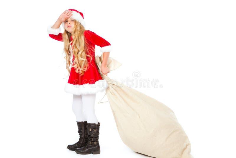 Mlle Santa épuisée de tirer le sac lourd à cadeau photographie stock
