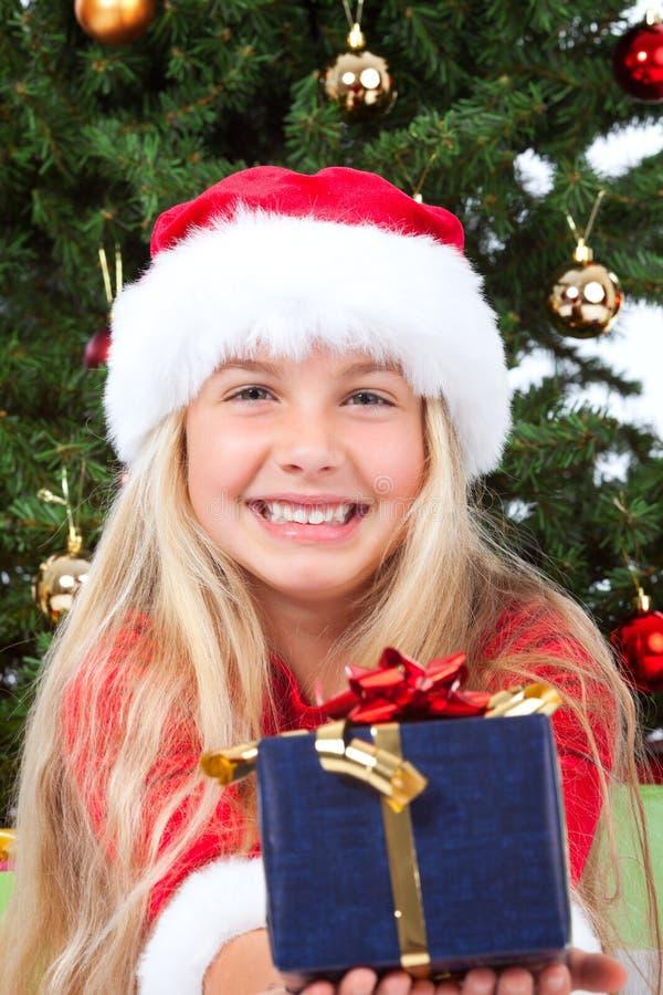 Mlle Santa retenant un cadeau et un sourire image stock