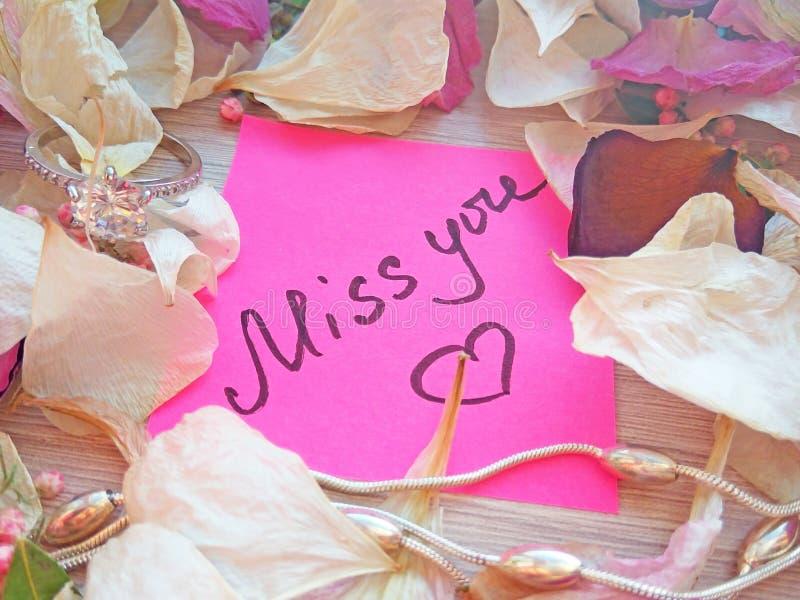 Mlle vous message sur la note collante rose avec les pétales secs de fleur de rose et d'orchidée et l'anneau et la chaîne argenté photos stock