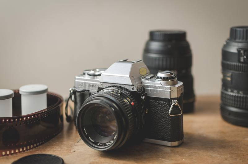 35mm analog camera surrounded with lenses and film on a table. Horizontal view of a vintage 35mm analog camera surrounded with lenses and film on a table royalty free stock images
