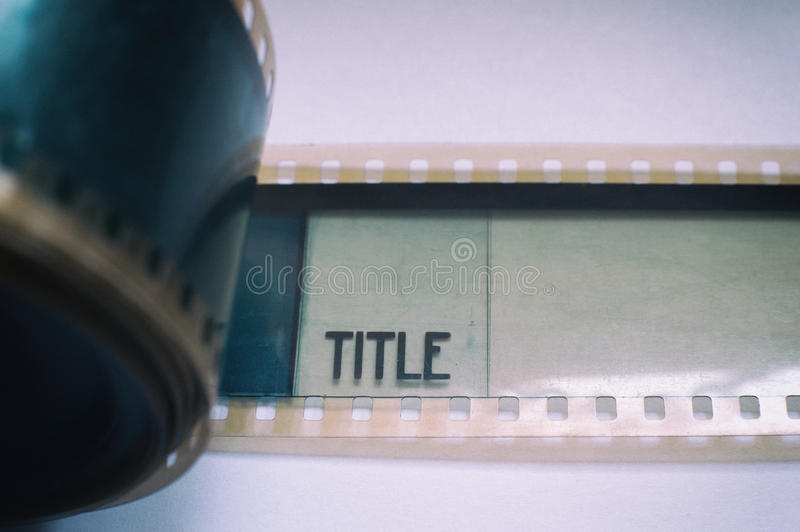 35 mm film frame title label close up. Detail of 35 mm film with title label printed on frame with reel on the left macro close up selective focus royalty free stock images