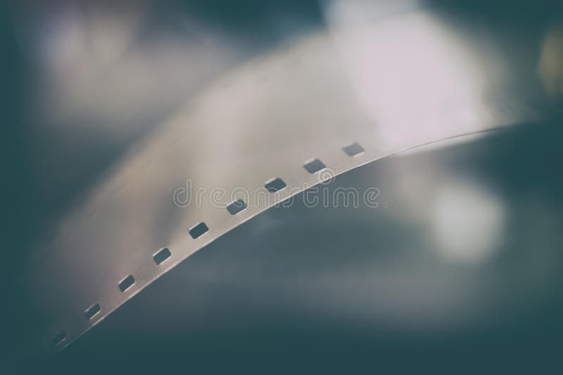 35 mm film reel extreme close up, movie symbol. Movie symbol: detail of 35 mm film reel with frame and focus on perforations macro close up royalty free stock photography