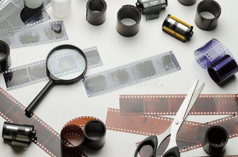 35mm fotografisk film, förstoringsglas och sax på vit bakgrund arkivbild