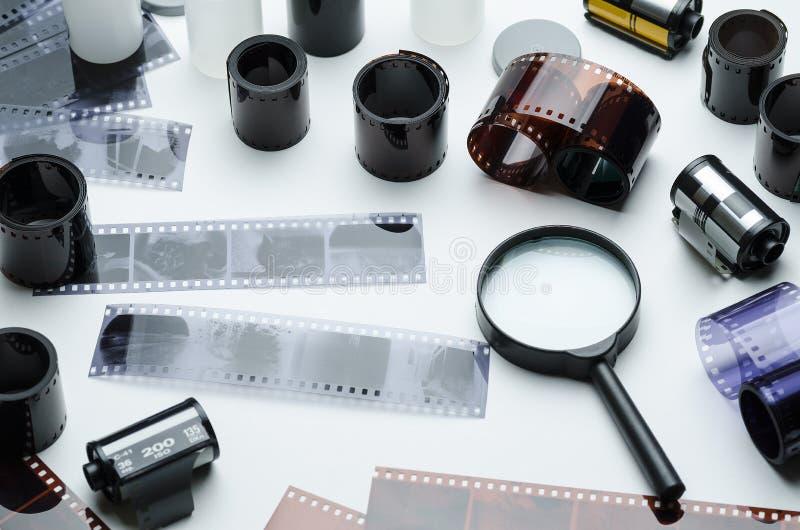 35mm fotografisk film och förstoringsglas på vit bakgrund arkivfoto