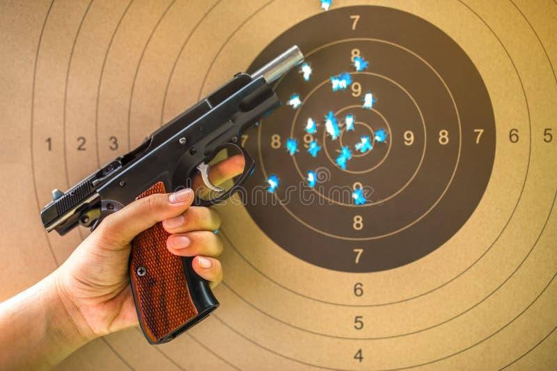 9 mm hand gun on bullseye target for shooting practice. royalty free stock photography