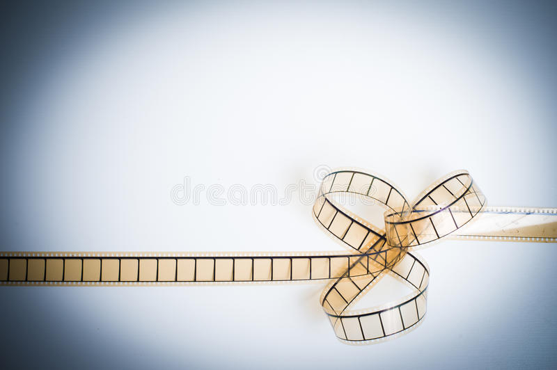35mm movie filmstrip, film bow, copyspace vintage color look. 35mm movie filmstrip with film bow, empty frames copyspace vintage color look royalty free stock image