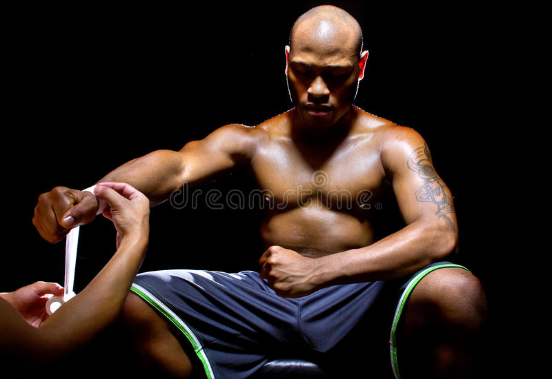 MMA Fighter or Boxer with Trainer Applying Athletic Tape. Motivated MMA fighter or Boxer with trainer applying athletic tape royalty free stock images