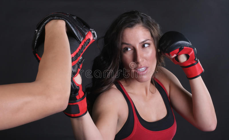 MMA Upper Cut. Beautiful Girl doing an upper cut punch into focus mitts royalty free stock images