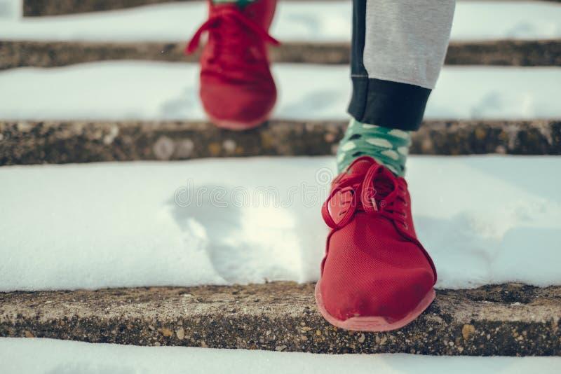 Mman i röda gymnastikskor som går ner den snöig trappan royaltyfri fotografi