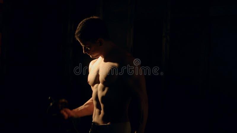 Mman z well - wyszkolony ciało, bicepsy, abs i Pecs, robimy ćwiczeniu z dumbbell obrazy stock