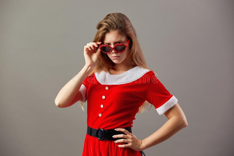 Mme avec du charme sérieuse Santa Claus dans des lunettes de soleil habillées dans la robe longue rouge et les supports blancs de image stock