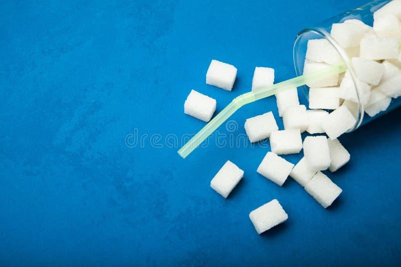 Mnóstwo białego cukieru sześciany spadali z szkła na błękitnym tle, opróżniają przestrzeń dla teksta zdjęcie royalty free