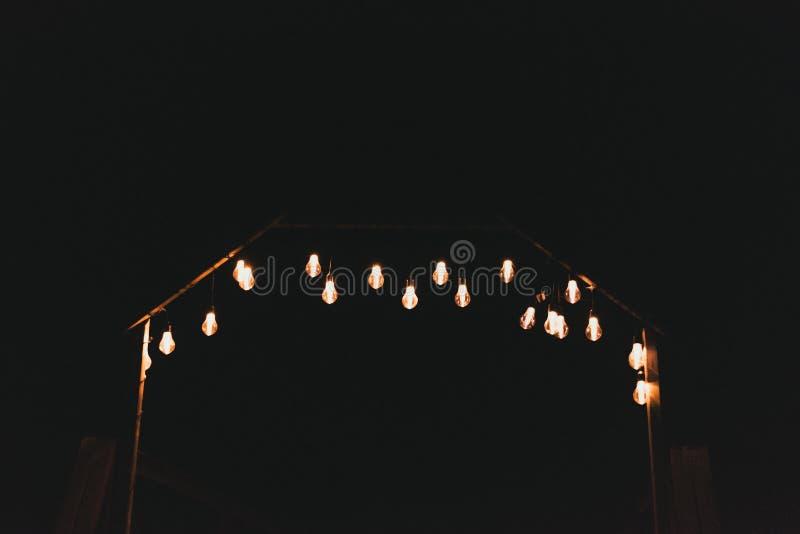 Mnóstwo elektryczne żółte żarówki na ulicie przy nocą Żarówki na girlandzie outside w zmroku zdjęcia royalty free