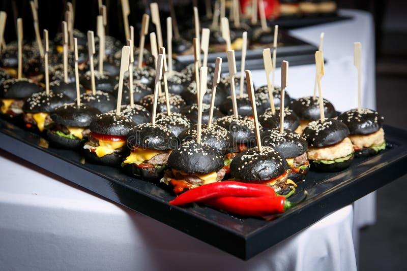 Mnóstwo mali czarni hamburgery na wydarzenie cateringu obraz royalty free