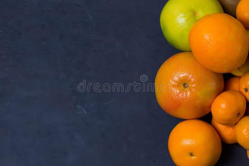 Mnóstwo pięknego jaskrawego cytrusa pomarańczowego mandarynu grapefruitowi sweeties lokalizują na prawo od wizerunku z krawędzią  zdjęcie stock