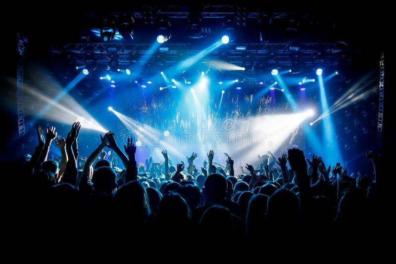Mnóstwo ręki, tłum na koncercie, błękita światło zdjęcia stock