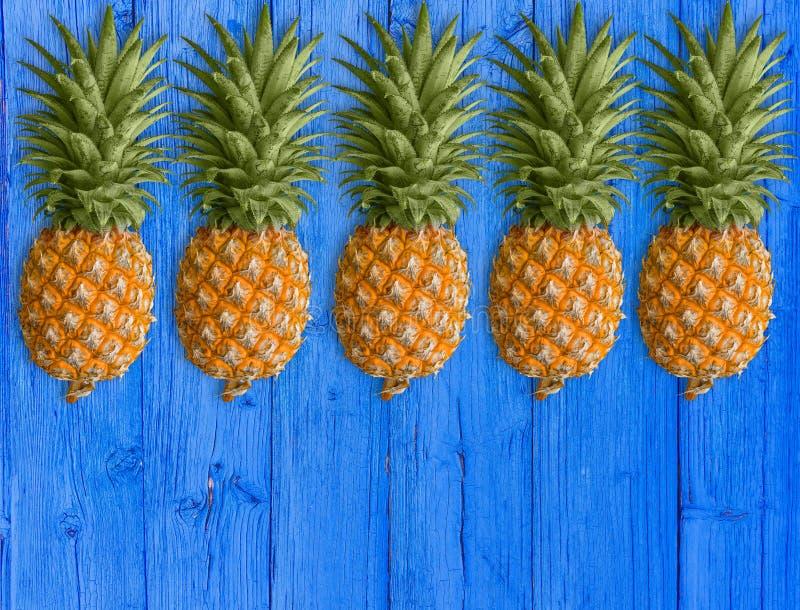 Mnóstwo tłustoszowaci ananasy na błękitnym drewnianym stole zdrowy ?ywienioniowy jedzenie obraz stock