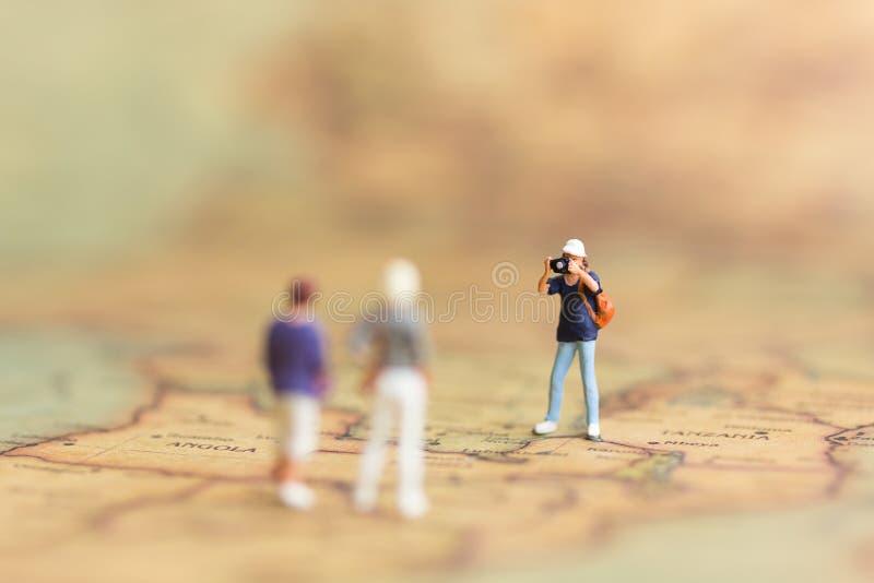 Mniature folk: Fotografer reser på världskartan, tar foto överallt Bruk som ett minnesbegrepp för lopp royaltyfria bilder