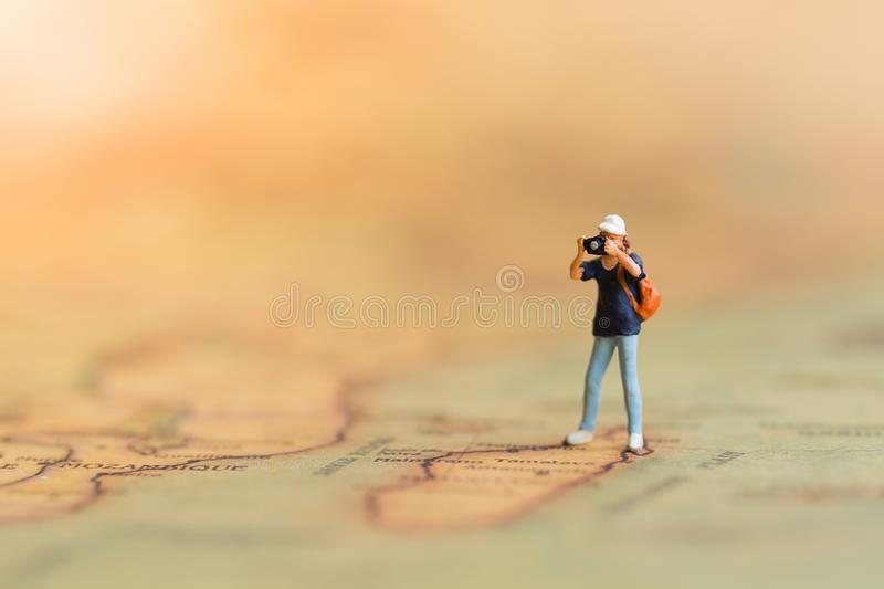 Mniature people: Photographers travel on the world map, take photos everywhere. stock images